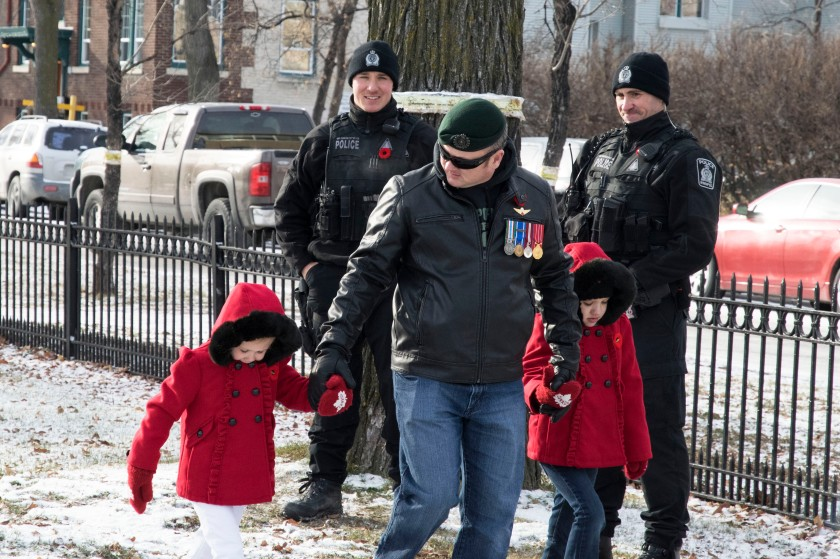 A veteran and his young children walk past members of the Winnipeg Police Service before the Remembrance Day Service at Vimy Ridge Memorial Park.
